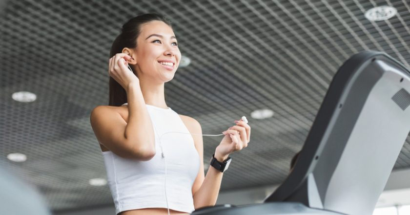 Prepare for training. Girl exercising on treadmill and listening music | © Milkos | Dreamstime Stock Photos