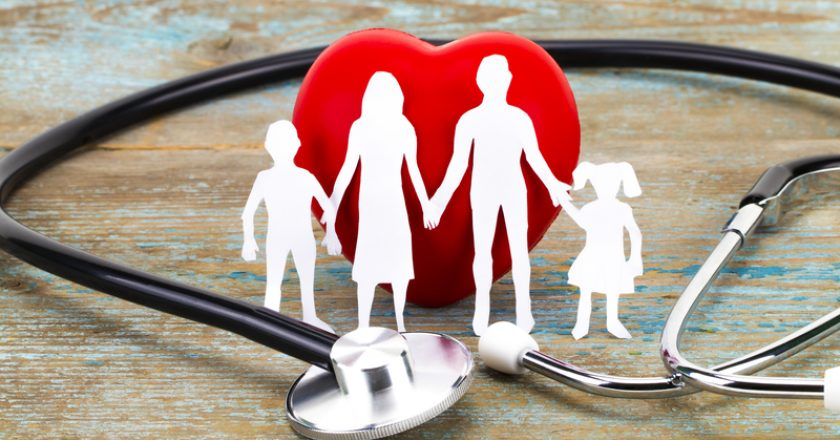 Paper silhouette of family, stethoscope and heart on wooden background. Health insurance concept | © Alexskp | Dreamstime Stock Photos