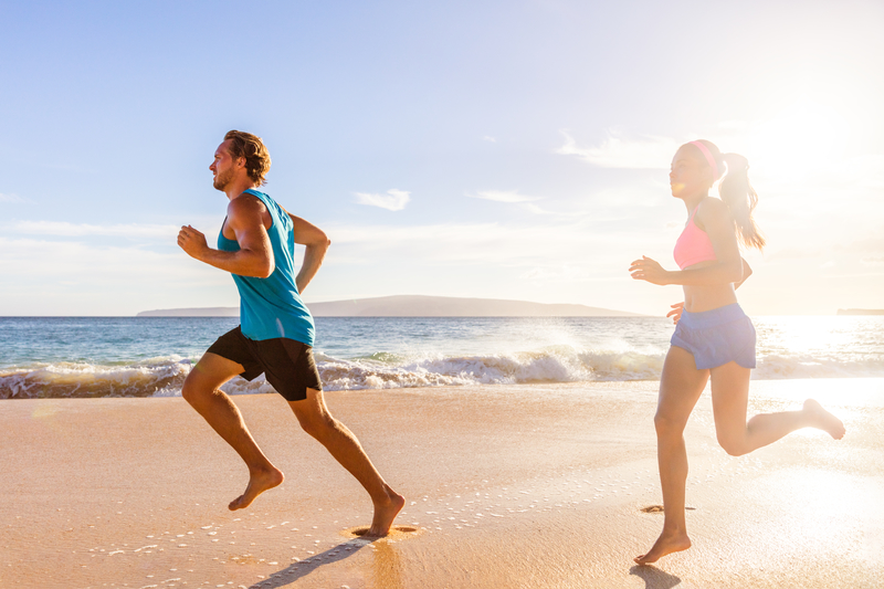 Jogging couple morning beach run healthy lifestyle. Active people training cardio workout together running barefoot in summer | © Martinmark | Dreamstime Stock Photos
