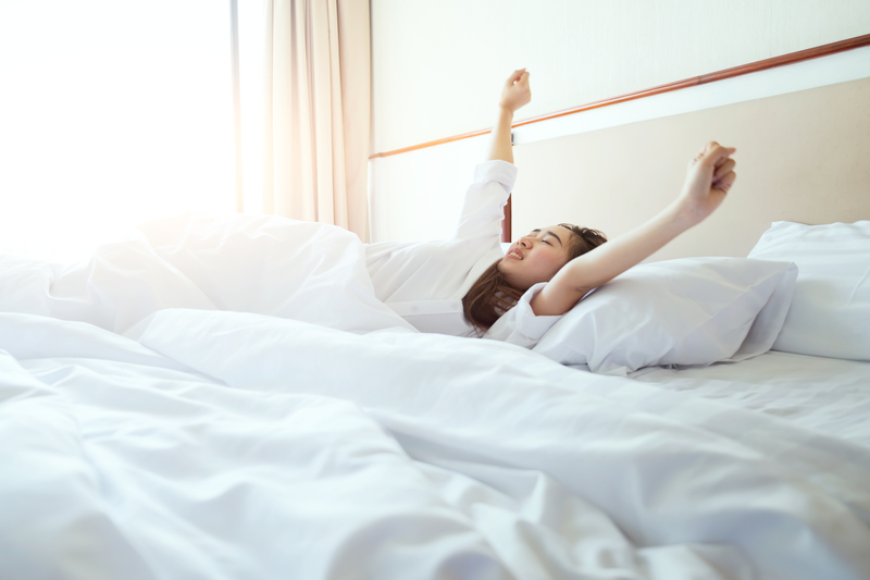 Woman stretching in bed after waking up, sunlight in morning | © Besttime | Dreamstime Stock Photos