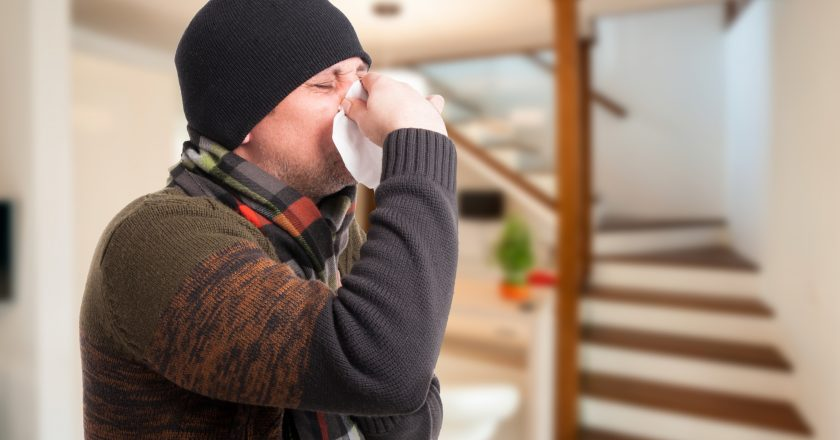 Man with sinus infection blowing his nose