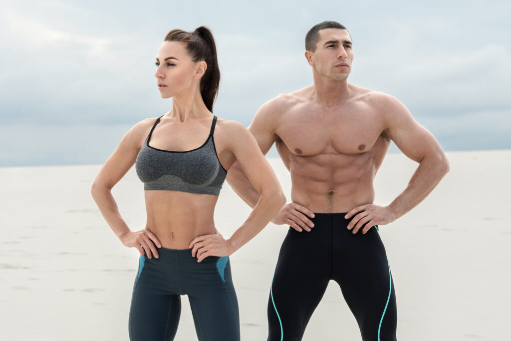 Sporty fitness couple showing muscle outdoors. Beautiful athletic man and woman, muscular torso abs