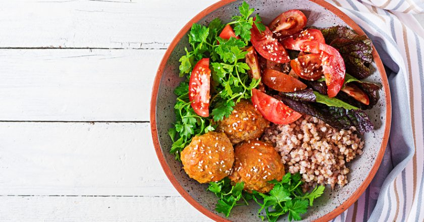 Meatballs, salad of tomatoes and buckwheat porridge on white wooden table. Healthy food. Diet meal. Buddha bowl. Top view. | © Timolina | Dreamstime Stock Photos