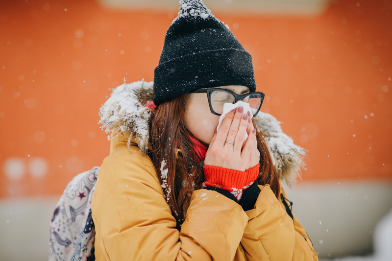 Woman blowing her nose into handkerchief. Young woman getting sick with flu in a winter day | © Uflypro | Dreamstime Stock Photos