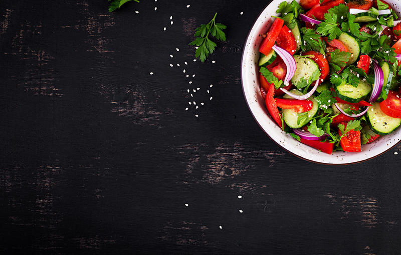 Tomato and cucumber salad with red onion, paprika, black pepper and parsley. Vegan food. Diet menu. Top view. Flat lay | © Timolina | Dreamstime Stock Photos