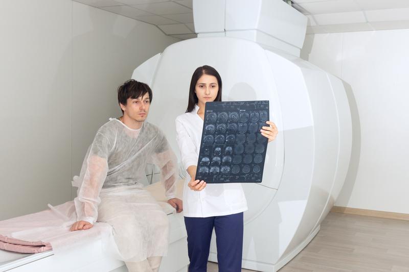Confident pleasant female doctor working with MRI scan results and tells the patient the diagnosis. magnetic resonance | © Luuuusa | Dreamstime Stock Photos