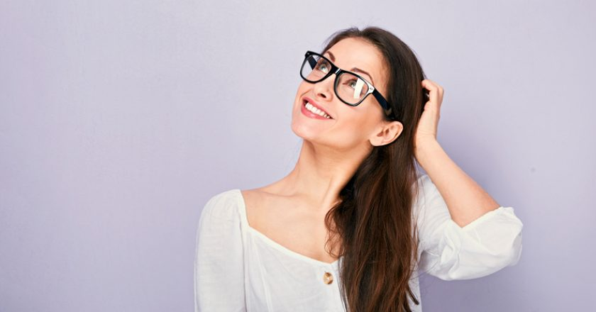 Beautiful positive young happy woman in eye glasses thinking and looking up in casual shirt on purple background | © Nastia1983 | Dreamstime Stock Photos