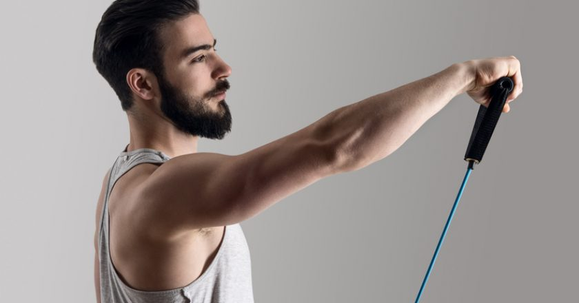 Young athlete in tank top workout with elastic resistance band doing shoulder exercises | © Sharplaninac | Dreamstime Stock Photos