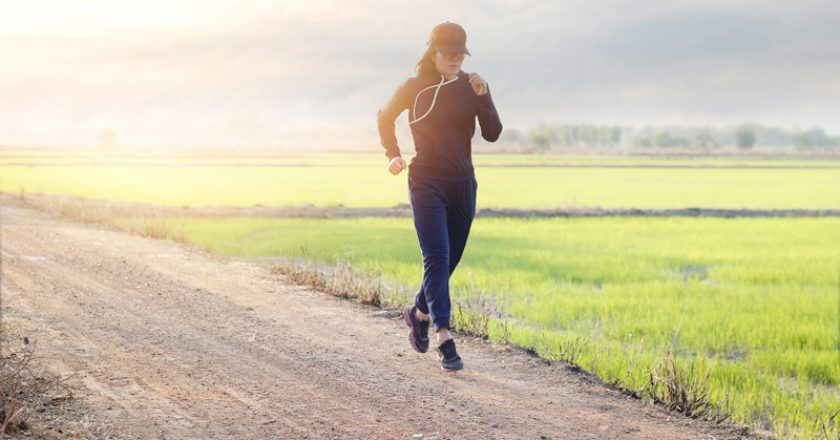 Woman running excercise on rural road of green field sunset back | © Ipopba | Dreamstime Stock Photos