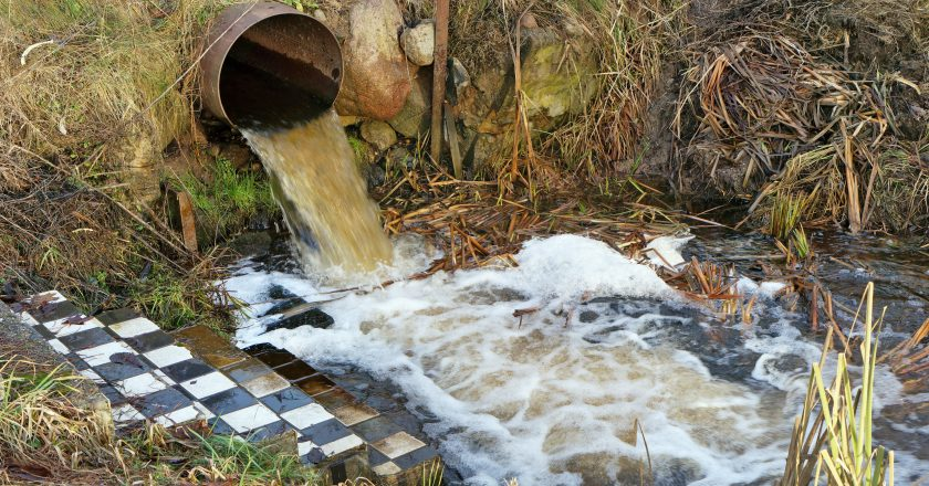 Dirty waste water merges into a clean forest stream
