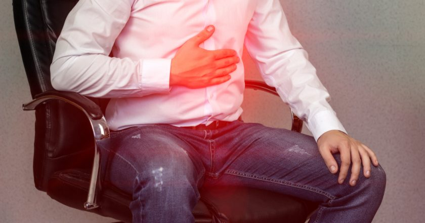 A man in a white shirt is sitting on a chair and holding on to the stomach, abdominal pain, heartburn