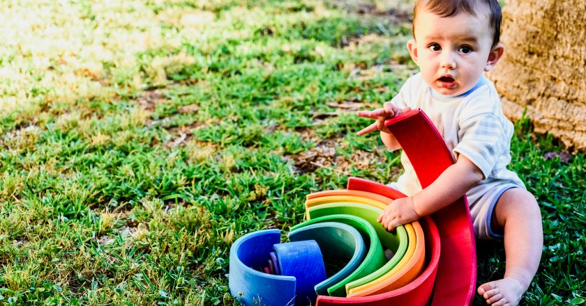 Baby playing with a colorful wooden rainbow on the grass, children`s intellectual and mental development