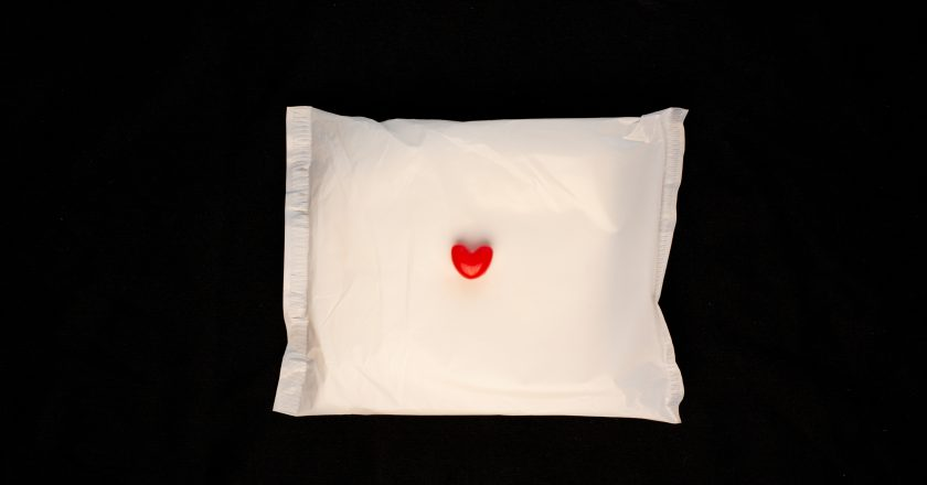 Irregular period concept. Menstrual cycle pad with red hearts on black background. Menorrhagia or heavy menstruation