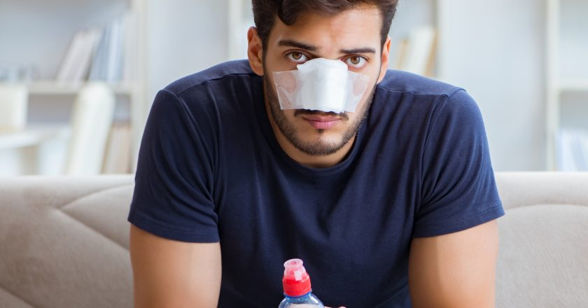 Young man recovering healing at home after plastic surgery nose