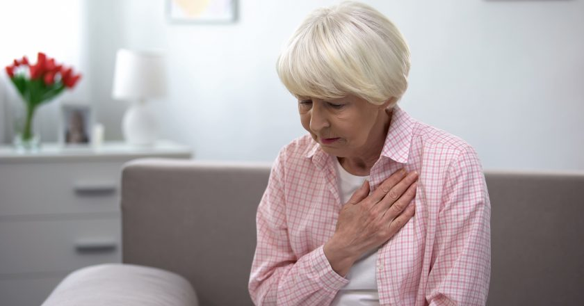 Old woman with heart disease holding hand on chest, suffering from tachycardia |