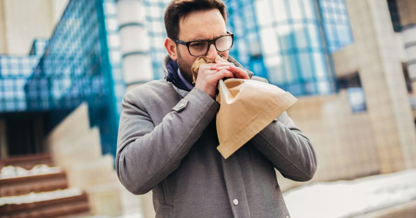 Businessman holding paper bag over mouth as if having a panic attack |