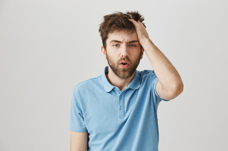 Funny mature bearded man with messy hair and beard, rubbing head and being tired or having hangover, standing over gray   © Nkkravchenko   Dreamstime Stock Photos