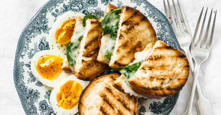 Healthy breakfast or snack - boiled farm eggs, spinach, grilled cheese sandwiches on light background |