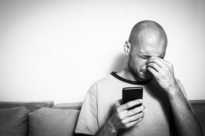 Severe migraine attack on the man after prolonged use of the mobile phone, black and white |