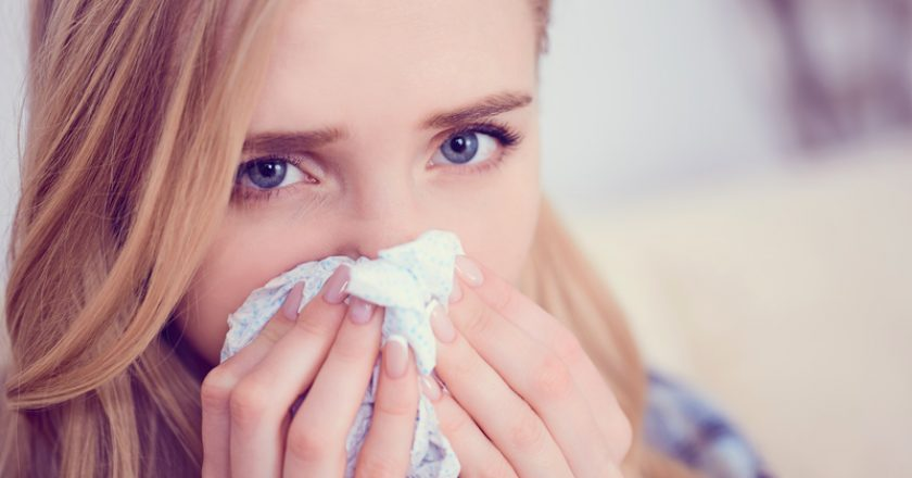 Young sick Caucasian woman sneeze at home on the sofa with a cold. Girl Used tissue paper blowing her nose. Medical and |