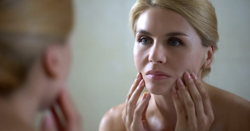 Upset woman looking in mirror and touching face, sad about skin aging, wrinkles |