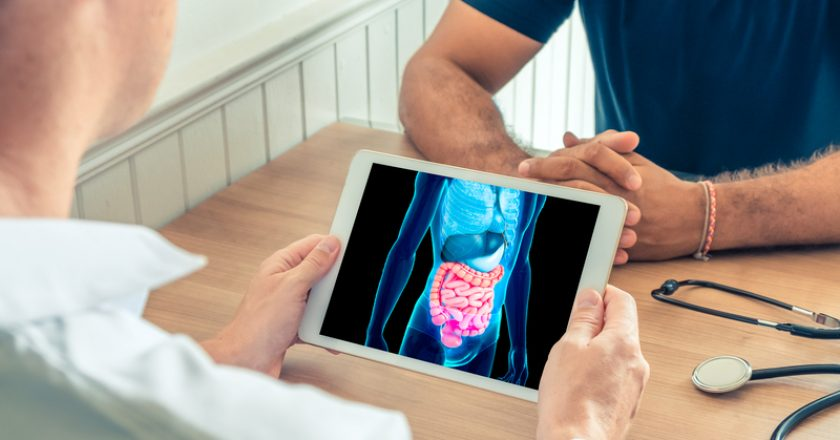 Doctor holding a digital tablet with technology 3D x-ray of intestine of the patient. Digestion and transit prevention |
