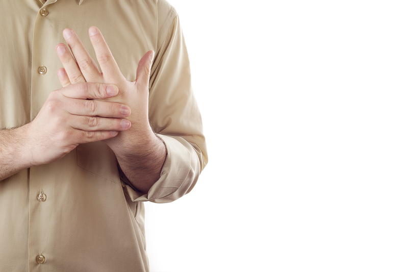 Closeup man feeling numbness and pain in his hands on white background |
