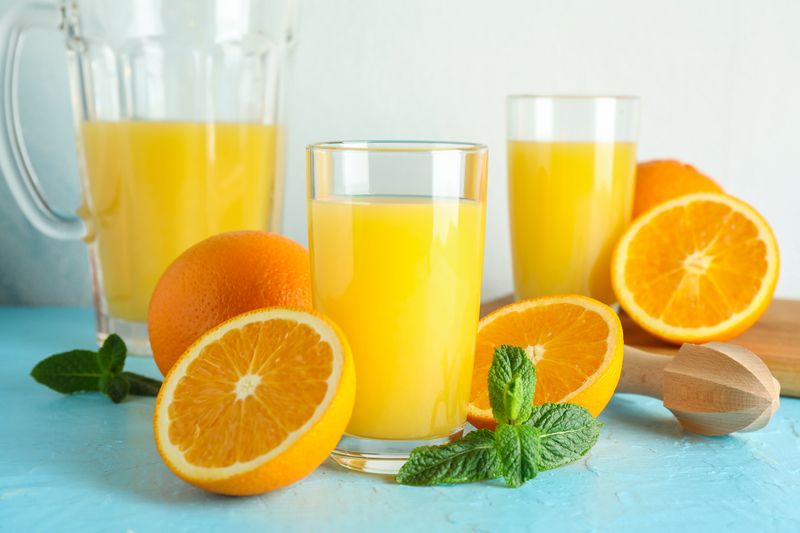 Composition with fresh orange juice in glassware, mint and wooden juicer on color table against white background, closeup |