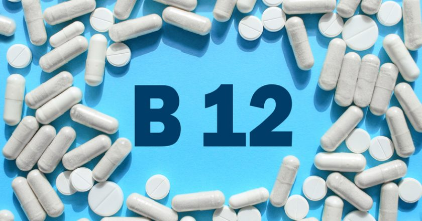 Vitamin B12 text in white capsules frame on blue background. Pill with cobalamin. Dietary supplements and medication |