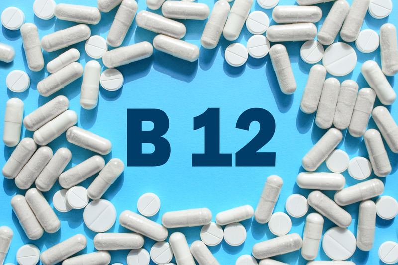 Vitamin B12 text in white capsules frame on blue background. Pill with cobalamin. Dietary supplements and medication  