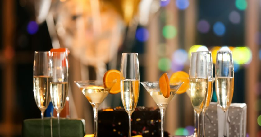 Glasses of alcohol with gift boxes on table at birthday party in club |