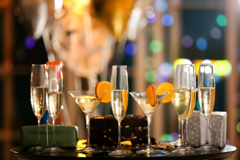 Glasses of alcohol with gift boxes on table at birthday party in club  