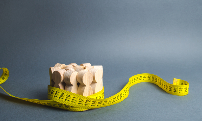 A crowd of wooden figures Gripped by measuring tape. Social Sciences. Promotion of ideas for weight loss, lifestyle. Information | © Andreyyalansky19 | Dreamstime Stock Photos
