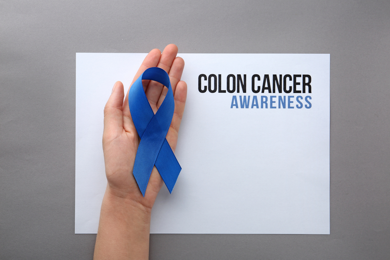 Woman holding blue ribbon near card with words COLON CANCER AWARENESS on grey background, top view |