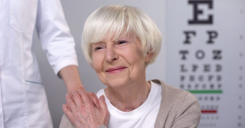 Optician comforting elderly woman during eyesight examination, health care  