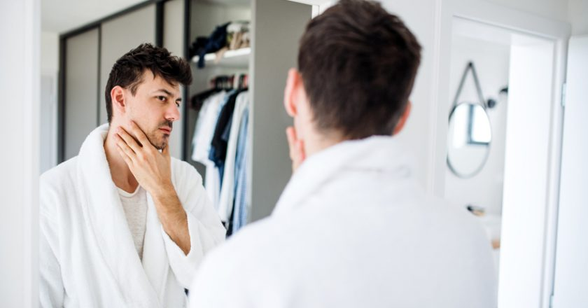 Young man looking in mirror in bedroom in the morning, daily routine. |