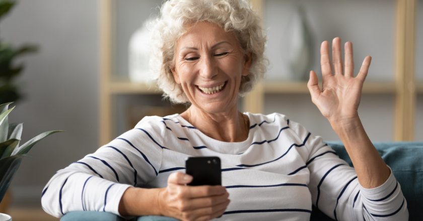 Elderly woman holding smartphone wave hand having videocall |