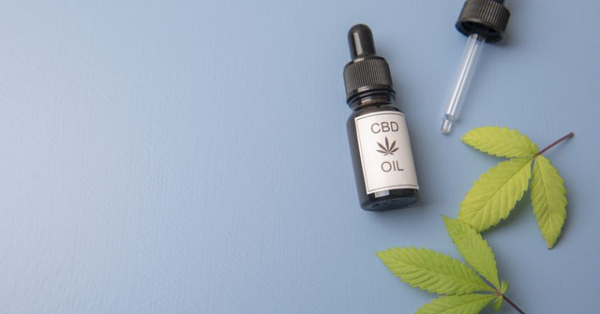 CBD oil in a dropper bottle with cannabis leaves and hemp seeds on a blue background |