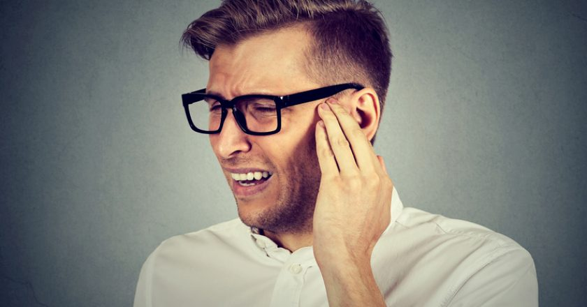 Tinnitus. Sick man having ear pain touching painful head |