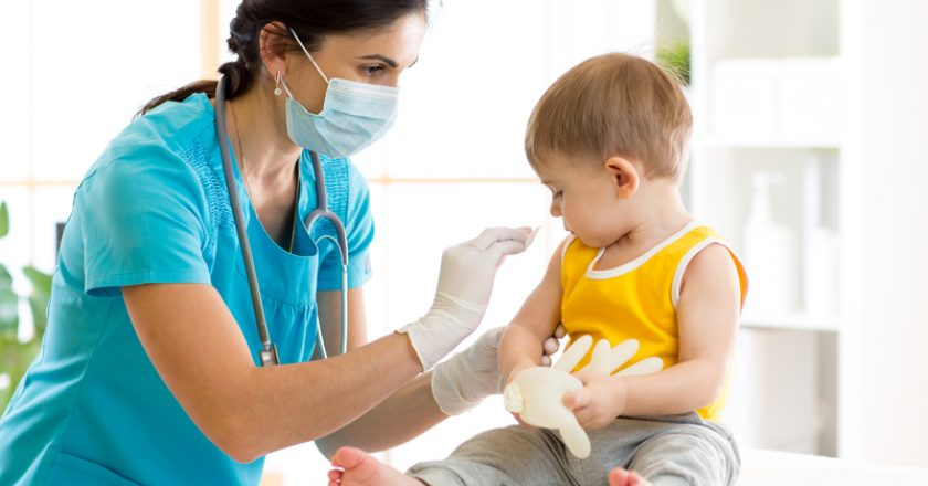 Doctor holds an injection vaccination the child |