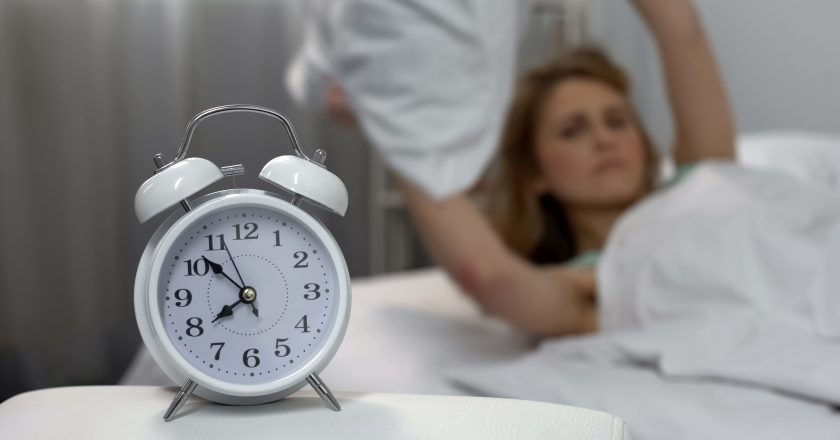 Annoyed with alarm clock lady throwing pillow, sleep deprivation, morning stress