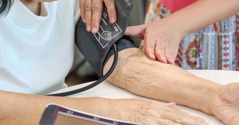 Daughter checking mother`s blood pressure hypertension