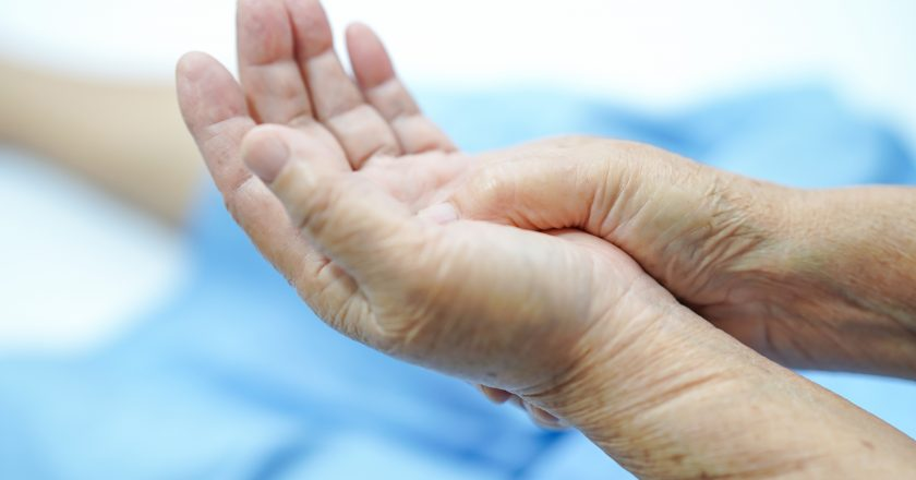 Asian senior or elderly old woman patient pain trigger finger lock her hand while sitting on bed in nursing hospital ward