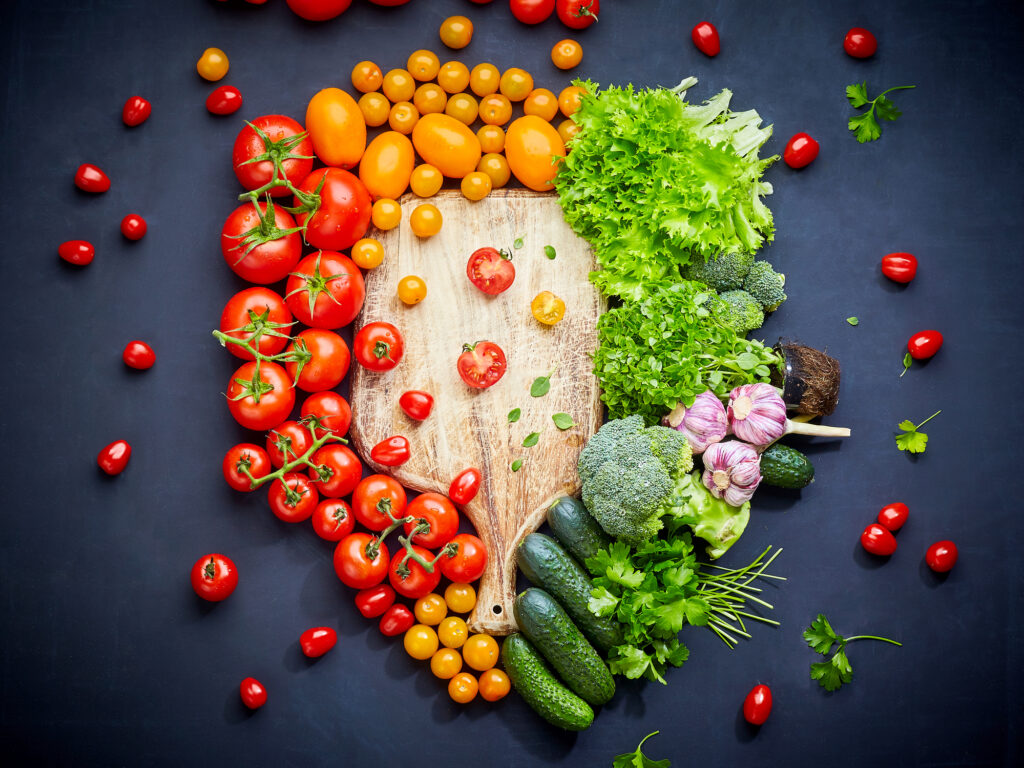 Colorful vegetables composition with red and yellow tomatoes, cucumbers, greens. Top view.  