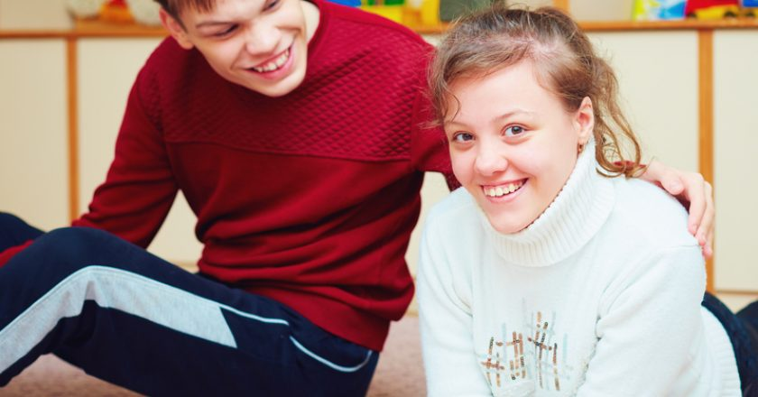Smiling teenage friends with special needs talking cheerfully together in rehabilitation center | © Olesiabilkei | Dreamstime Stock Photos