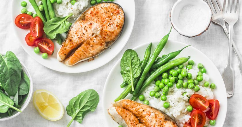 Healthy balanced mediterranean diet lunch - baked salmon, rice, green peas and green beans on a light background, top view |