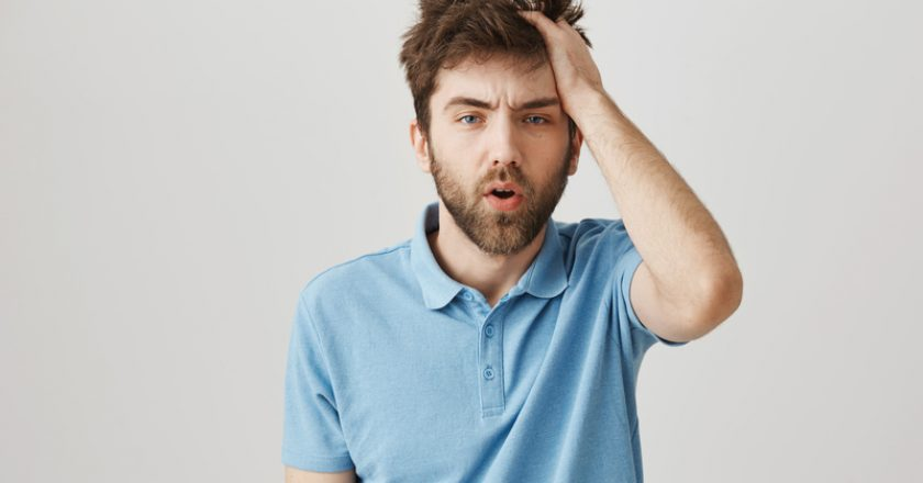 Funny mature bearded man with messy hair and beard, rubbing head and being tired or having hangover, standing over gray | © Nkkravchenko | Dreamstime Stock Photos