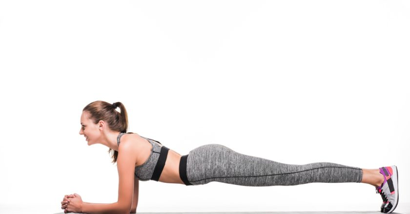 side view of smiling sportswoman doing plank exercise on yoga mat | © Lightfieldstudiosprod | Dreamstime Stock Photos