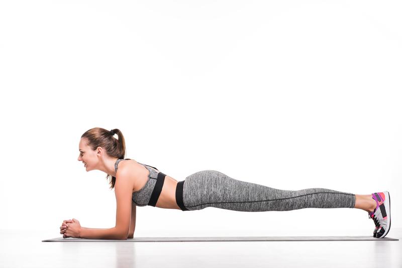 side view of smiling sportswoman doing plank exercise on yoga mat | © Lightfieldstudiosprod | Dreamstime Stock Photos