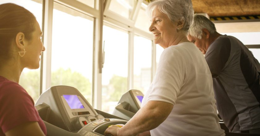 Personal trainer exercise helps elderly couple. | © Liderina | Dreamstime Stock Photos